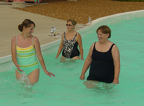women smiles and talk while walking in waist deep water in the lazy river