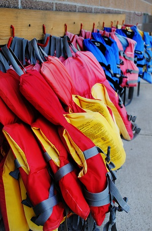 A row of multi-colored life jackets hanging on hooks