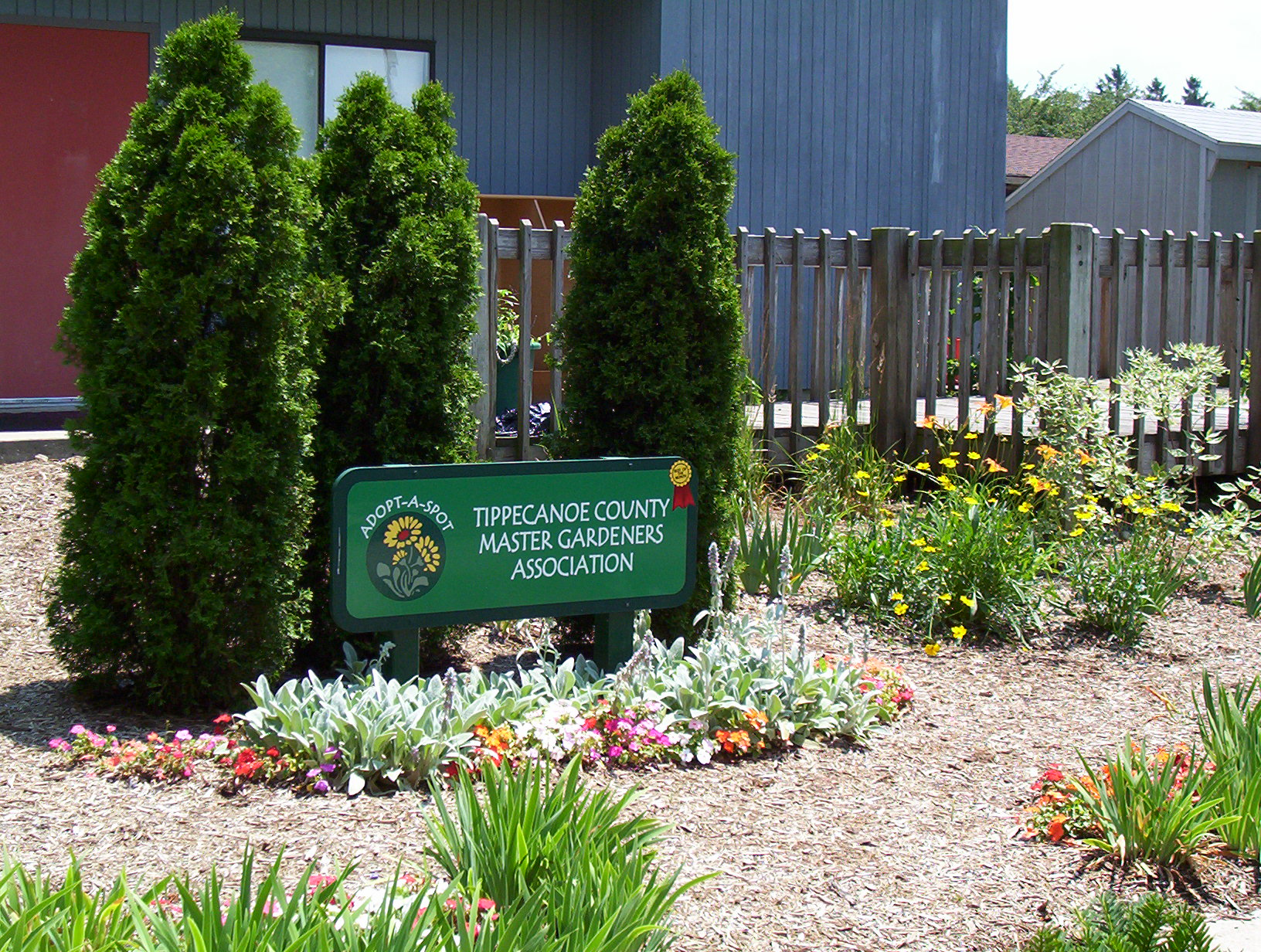 Garden of flowers, trees, and a sign indicating the sponsor
