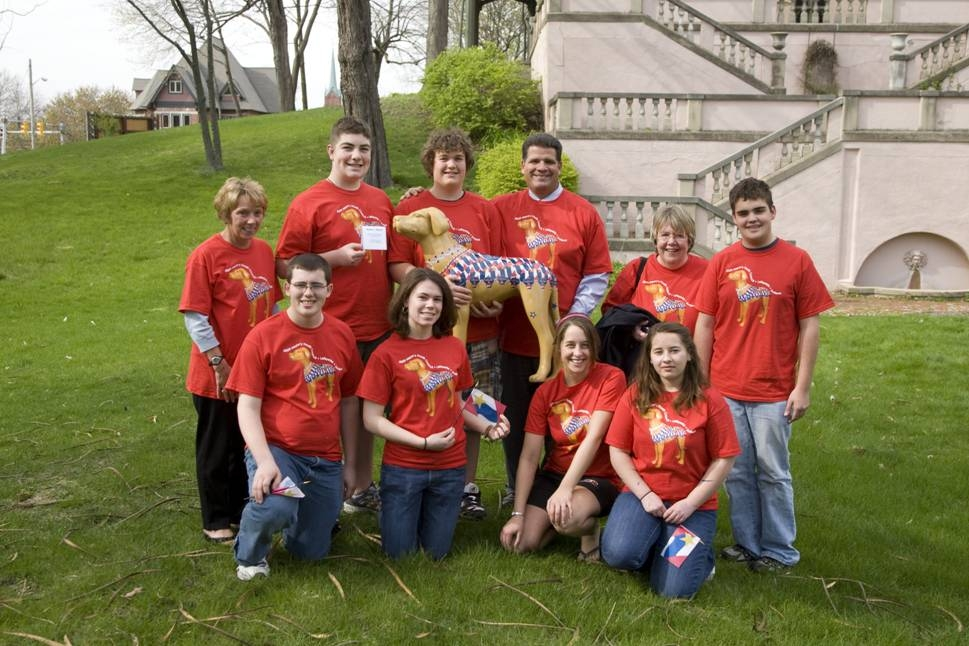 A group of teenagers in red shirts holding a plastic dog