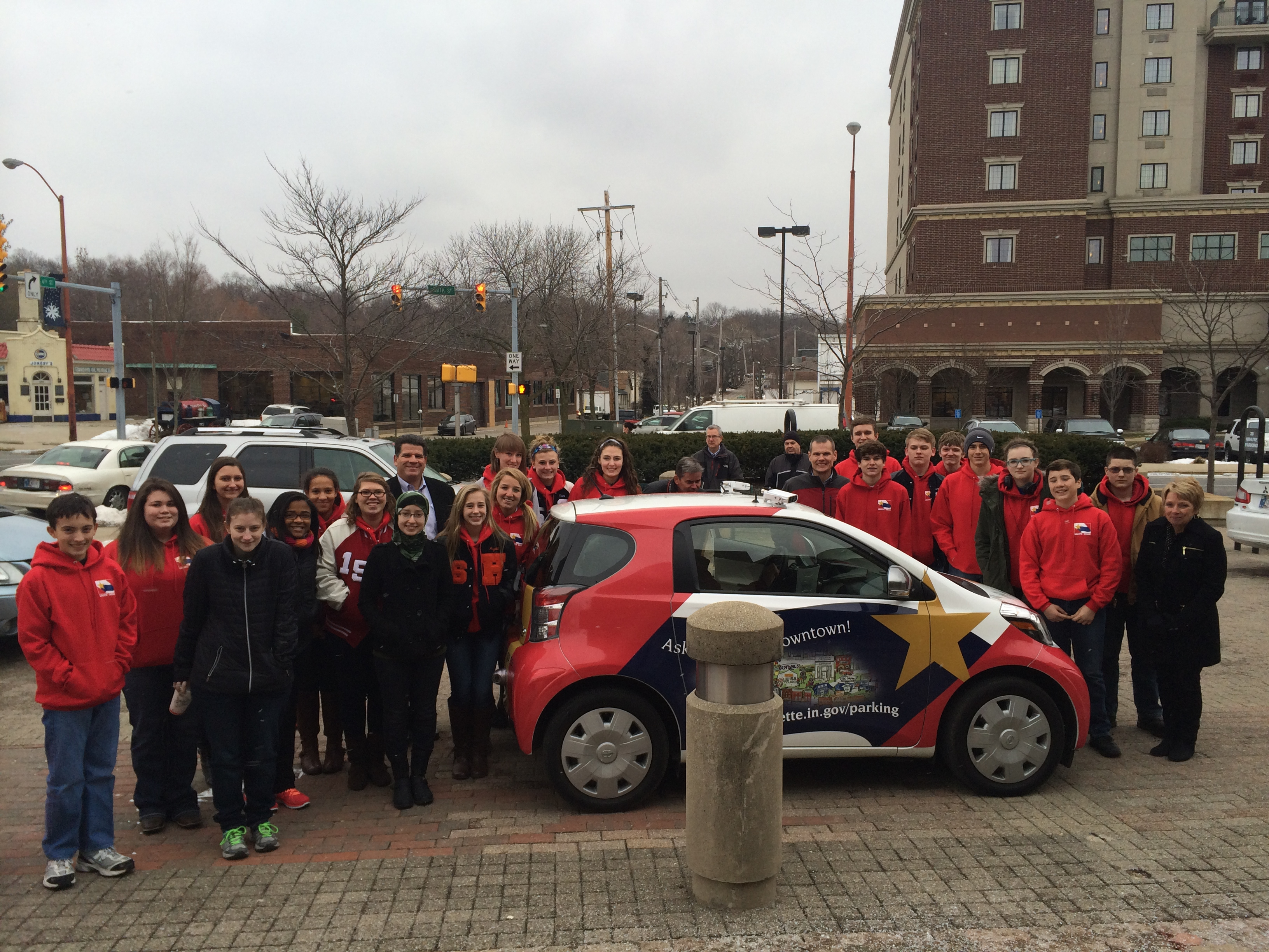 A group of teenagers standing next to a smart car