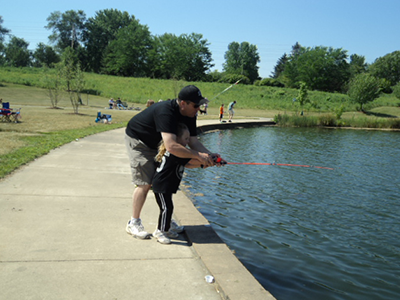 Adult helping kid fish