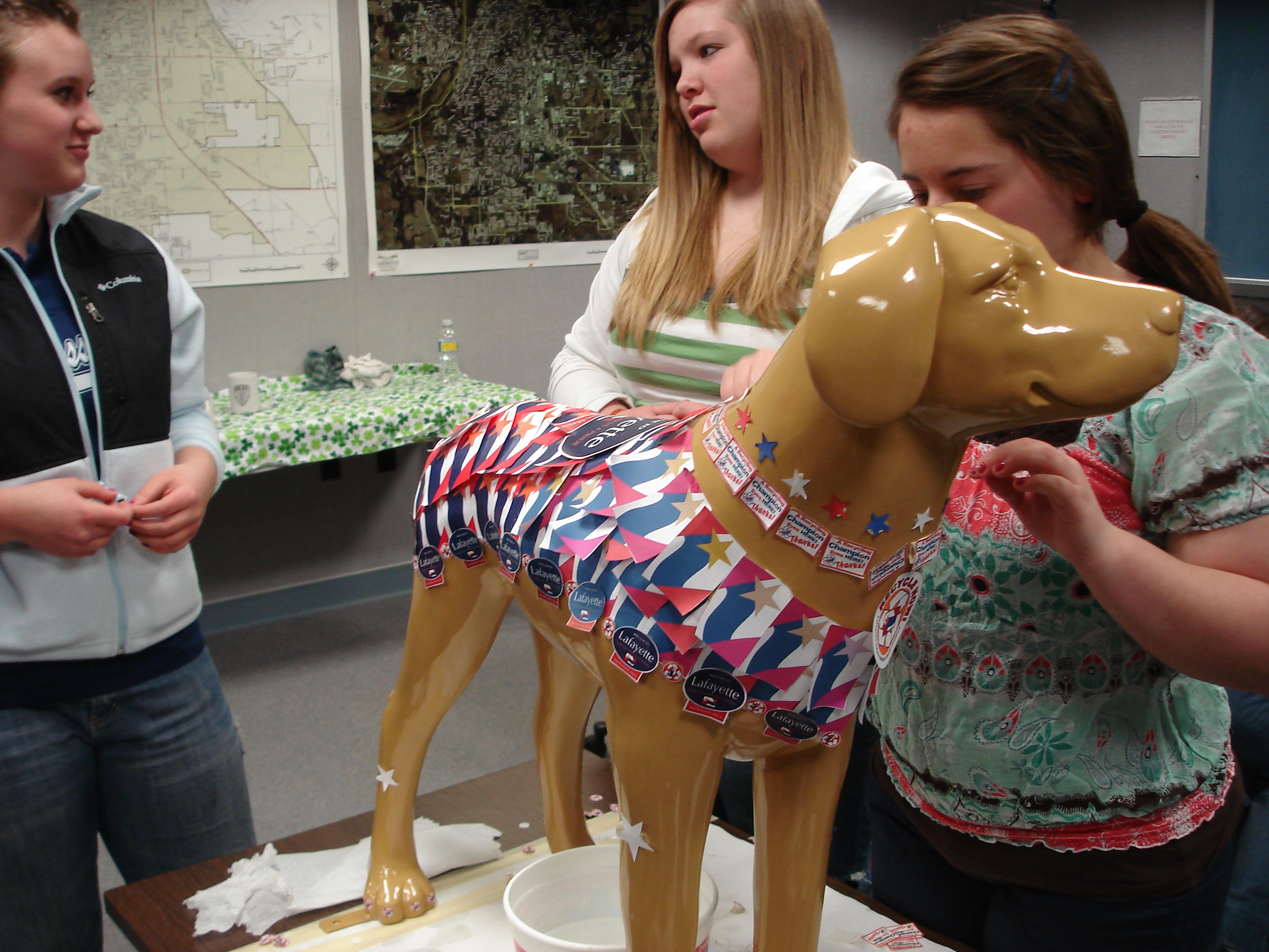 3 teens decorating a fake, plastic dog
