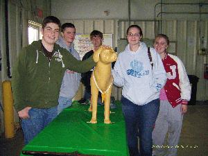 5 teenagers smiling next to a plastic dog