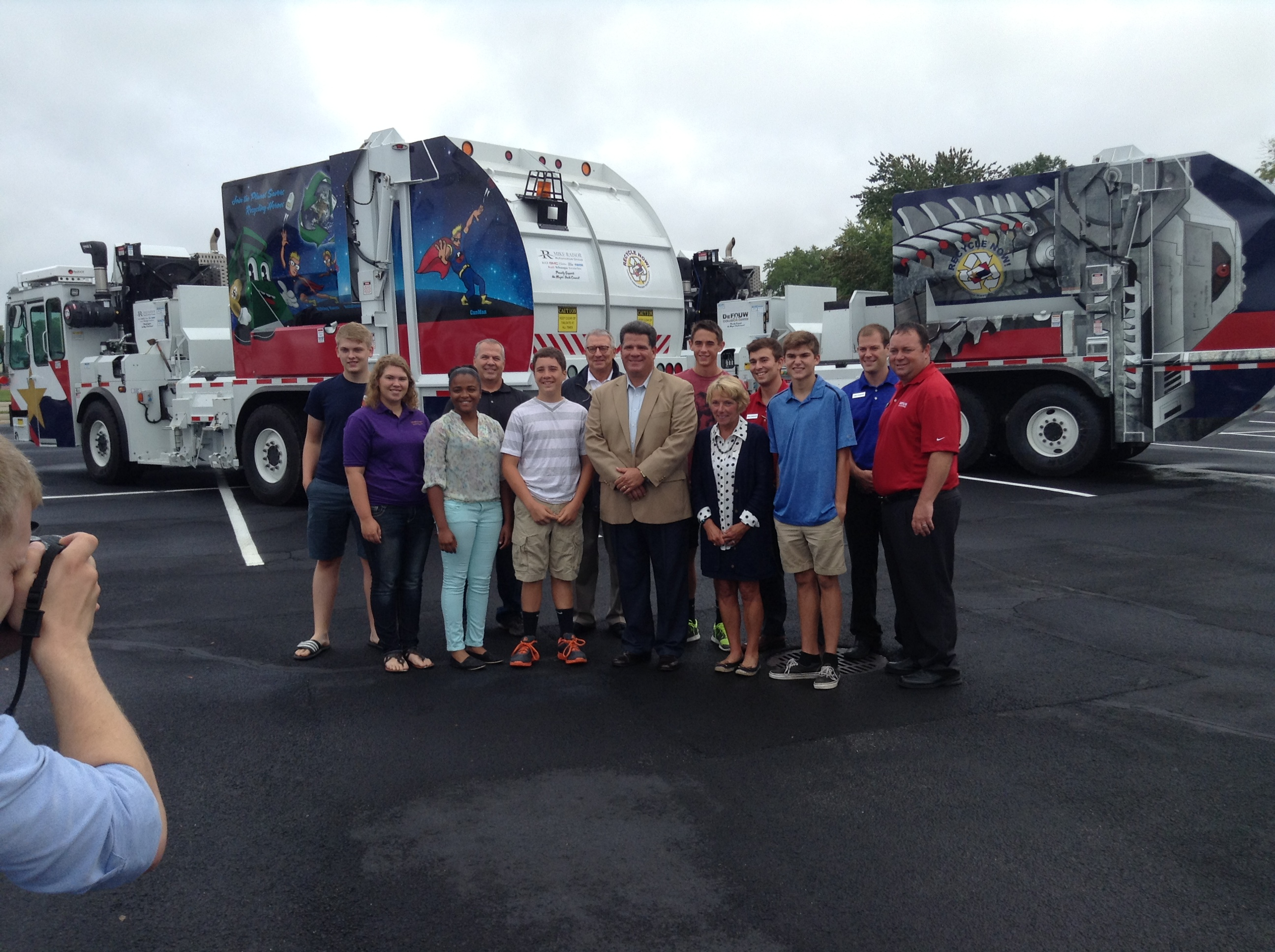 A group of people standing in front of brand new trash trucks