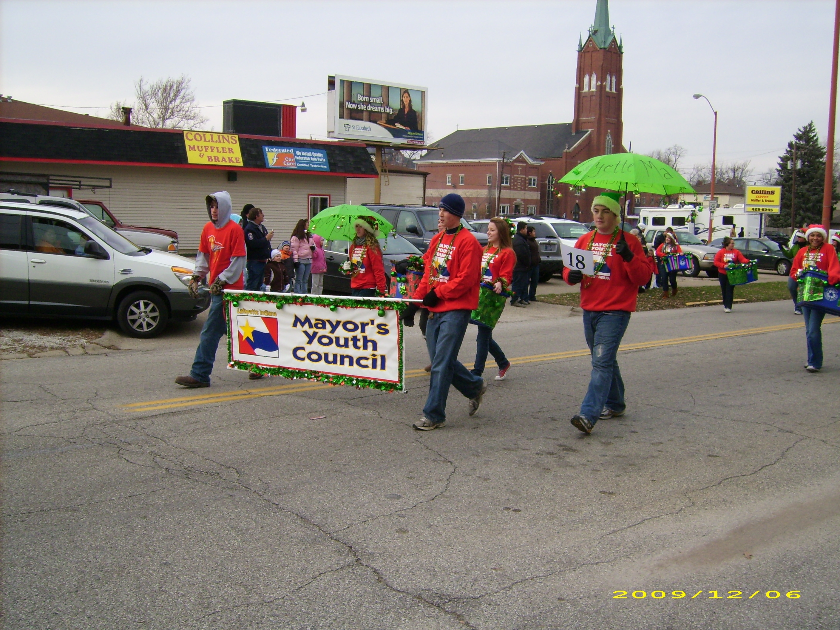 A group of teens in red shirts walking in a parade holding a sign