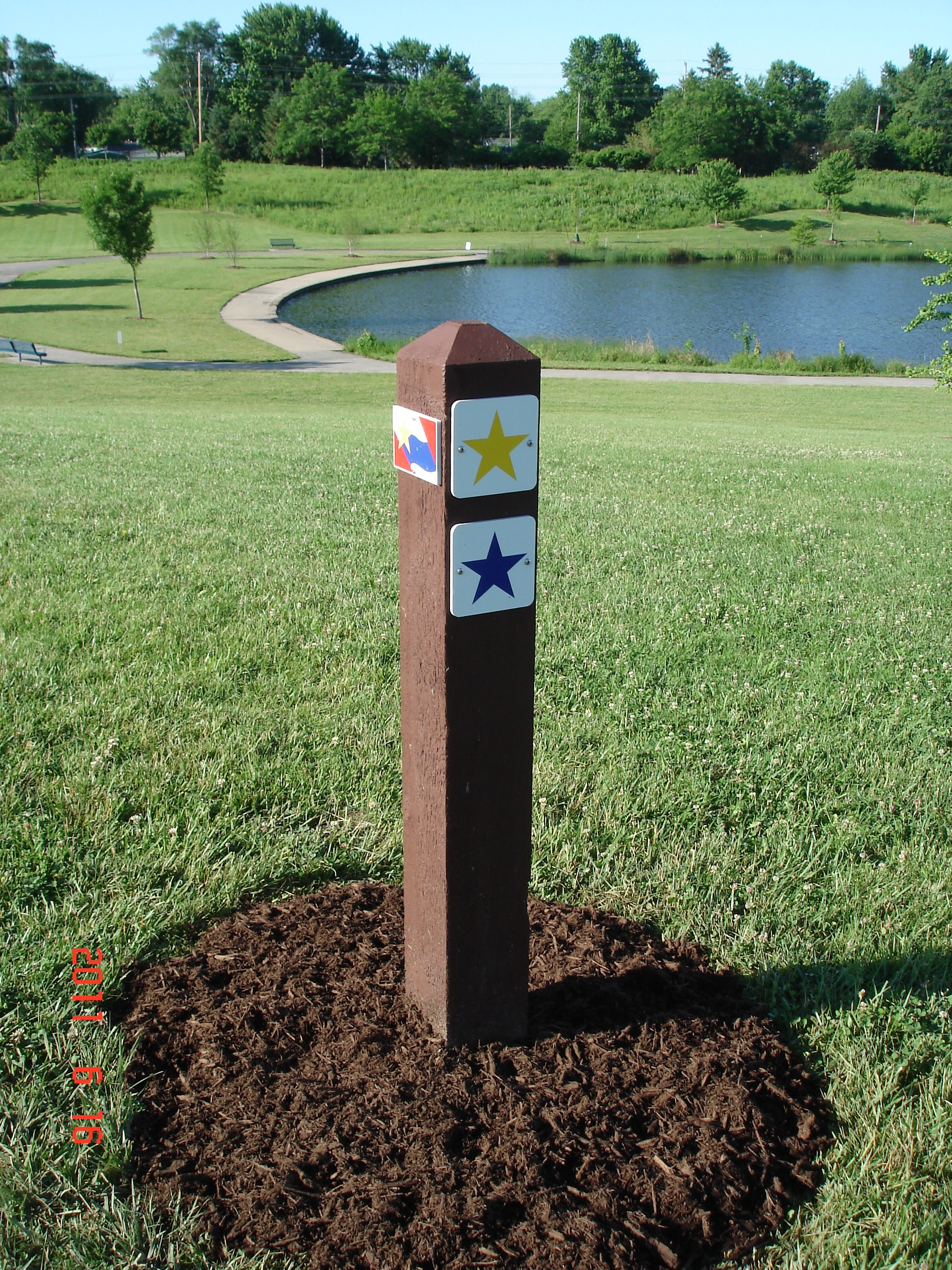 A wooden post with a yellow start and a blue star in the grass