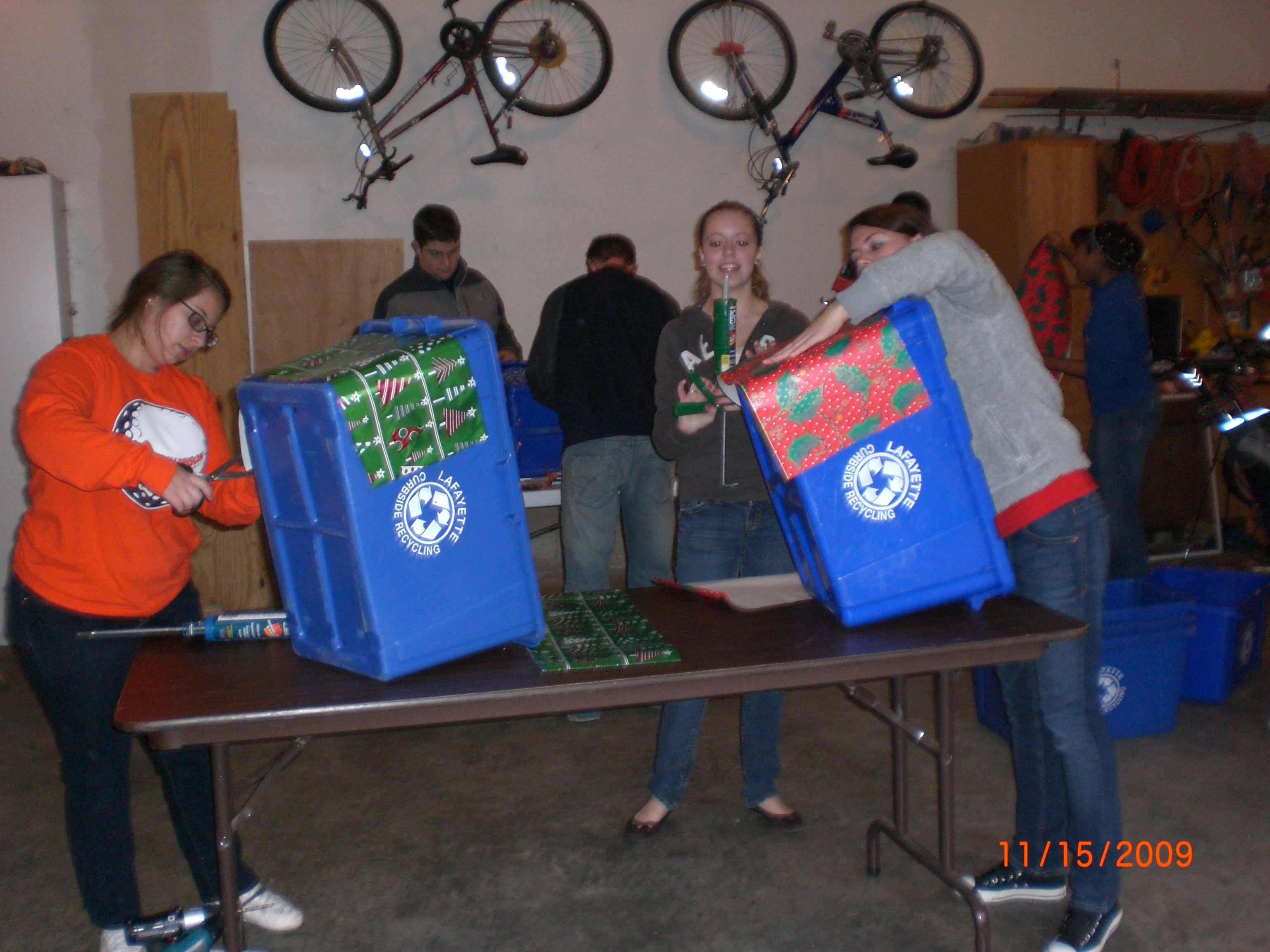 Teens decorating recyling bins for Christmas