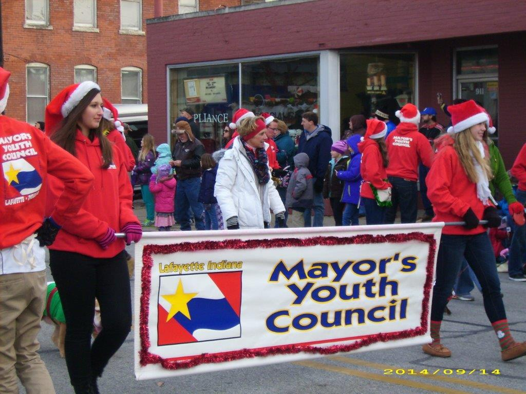 Teens holding a Mayor's Youth Council banner in a parade